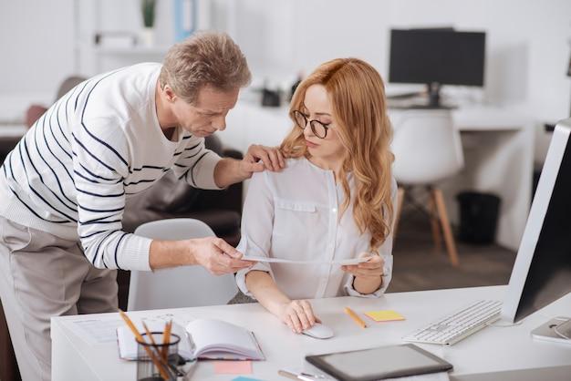 Wykwalifikowany doświadczony dojrzały kierownik biura stojący w biurze podczas pracy nad projektem i dotykający ramienia młodych kolegów