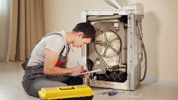 Wykwalifikowany mechanik pisze w schowku, sprawdzając zepsutą pralkę ładowaną od góry na podłodze w zbliżeniu pokoju