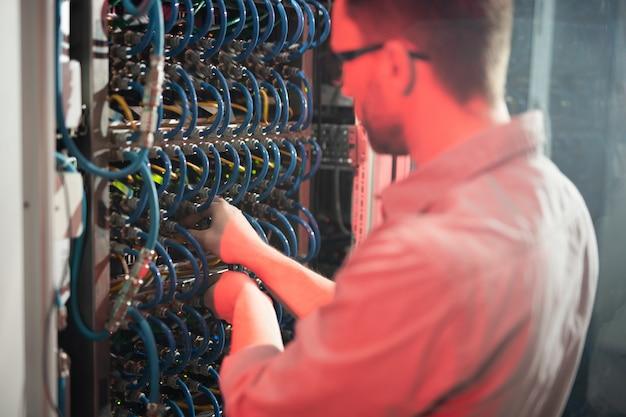 Wykwalifikowany mężczyzna naprawia serwer