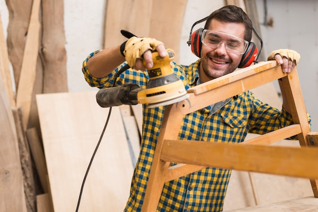 Wykwalifikowany stolarz używa szlifierki mechanicznej jako narzędzia do polerowania swoich mebli