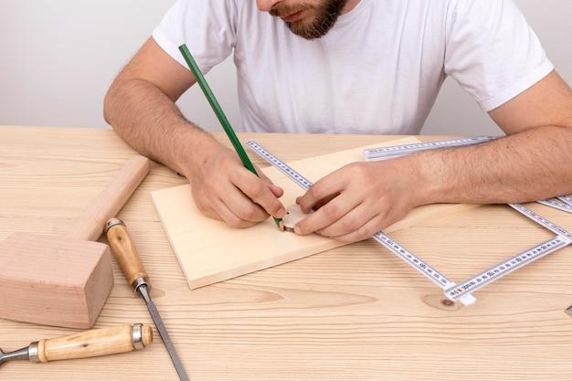 Wykwalifikowany stolarz za pomocą swoich narzędzi na drewnie