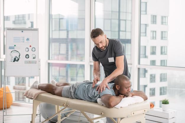 Wykwalifikowany terapeuta. profesjonalny miły lekarz wykonuje masaż pleców dla swojego pacjenta podczas wykonywania swojej pracy