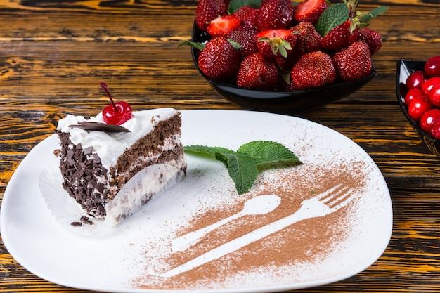 Wykwintna prezentacja ciasta czekoladowego zwieńczonego świeżą śmietaną i wiśnią ozdobioną konturami łyżki i widelca w proszku czekoladowym dla dekoracyjnego detalu, z tyłu świeże jagody