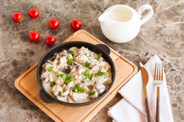 Wykwintne danie z białych grzybów w śmietanie z przyprawami na patelni na marmurowym tle.
