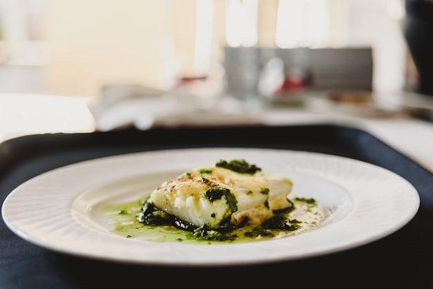 Wykwintne danie z pieczonej ryby elegancko platerowane.