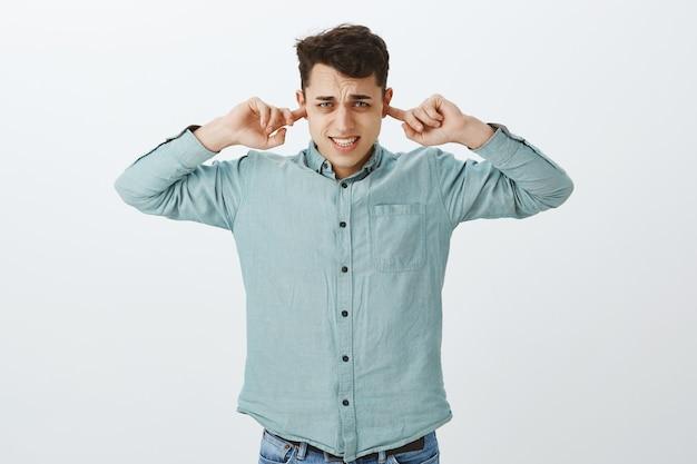 Wyłącz irytującą piosenkę. niezadowolony niewygodny europejczyk w zwykłej koszuli