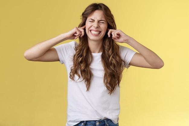 Wyłącz tę okropną muzykę. dziewczyna robiąca krzywą twarz przymknęła uszy palce wskazujące zatkane dziurki w uszach zamknęła oczy zaciskała zęby niezadowolona zirytowana głośny okropny hałas podrażniony od sąsiadów żółtym tle.