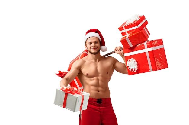 Wyłącznie dla ciebie. stonowany mężczyzna fitness bez koszuli w czapce świętego mikołaja, niosący ciężary z prezentami, trzymający prezent, patrzący radośnie i uśmiechający się do kamery, 2018, 2019.