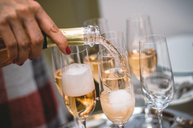Wylewanie musującego żółtego szampana na kieliszki do wina