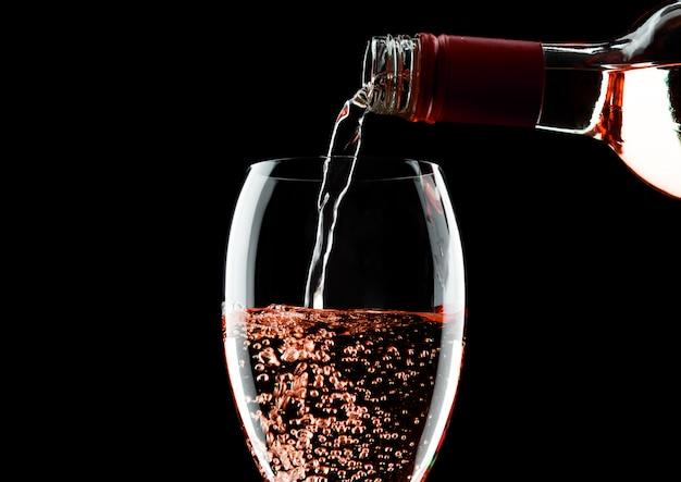 Wylewanie różowego wina różowego z butelki do szklanki na białym tle