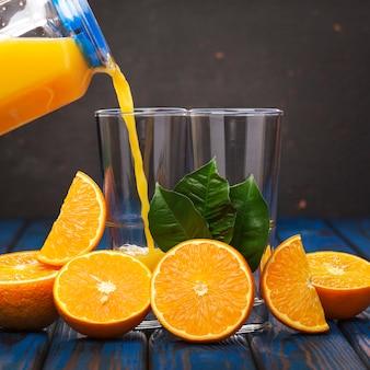 Wylewanie soku pomarańczowego. świeżo wyciśnięty sok pomarańczowy. zdrowe odżywianie