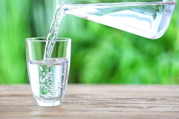 Wylewanie świeżej wody do szklanki na stole na zewnątrz