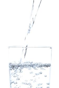 Wylewanie wody pitnej do szkła na białym tle.