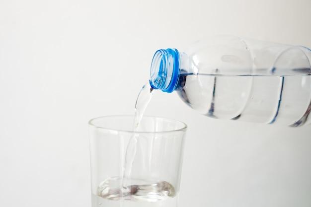 Wylewanie wody pitnej w szklanym białym tle