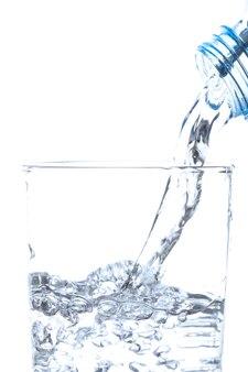 Wylewanie wody pitnej z butelki do szkła na białym tle.