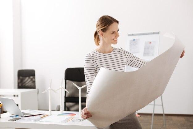 Wymarzona praca. pozytywna piękna kobieta trzyma plan i siedzi w biurze, ciesząc się swoim projektem