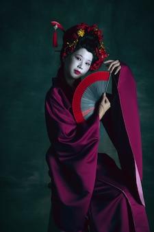 Wymarzone. młoda japonka jako gejsza na białym tle na ciemnozielonej ścianie. styl retro, porównanie koncepcji epok. piękna modelka jak jasny historyczny charakter, staromodny.