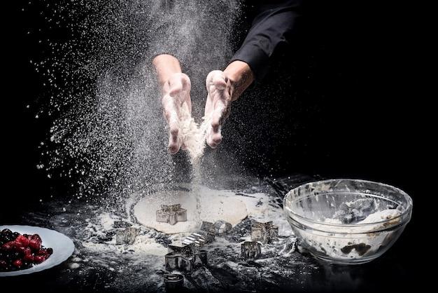 Wymarzony deser. bliska młodych mans ręce robiąc ciasteczka przy użyciu form piekarniczych i pracy jako szef kuchni.