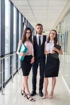 Wymarzony młody zespół trzech profesjonalnych biznesmenów, którzy omawiają papierkową robotę w nowoczesnym korytarzu biurowym