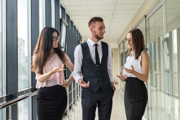 Wymarzony młody zespół trzech profesjonalnych ludzi biznesu, którzy omawiają papierkową robotę w nowoczesnym korytarzu biurowym
