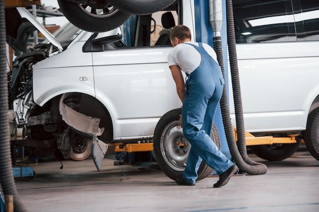 Wymiana opon. pracownik w niebieskim mundurze pracuje w salonie samochodowym