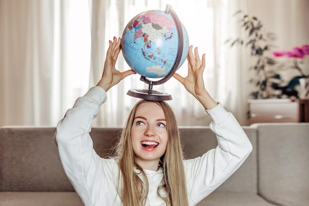 Wymiana studencka. koncepcja studiów za granicą. młoda radosna dziewczyna student marzy o podróży i trzyma kulę ziemską nad głową