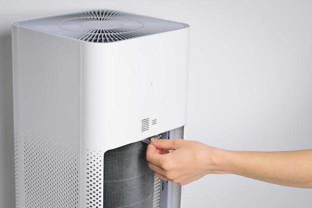 Wymieniono nowy filtr w oczyszczaczu powietrza zapobieganie alergiom pm 25 brudny filtr powietrza wymaga konserwacji wręcz mężczyźnie otworzyć pokrywę oczyszczacza powietrza sprawdź i wymień filtr w bocznej części powietrza