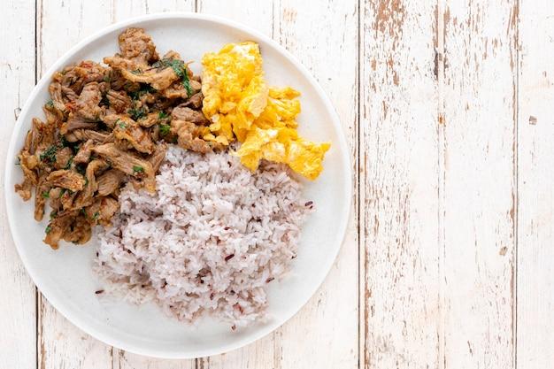Wymieszać smażoną wołowinę z liści bazylii drzewa, pieprz długi, indyjski pieprz długi, pieprz jawajski, pieprz, czosnek, chili obok jajecznicy i ryżu strumieniowego na białym tle tekstury drewna, widok z góry