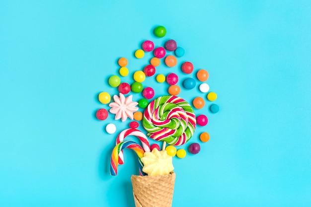 Wymieszaj kolorowe czekoladowe słodycze rozlane ze stożka lodów waflowych na niebieskim flat lay