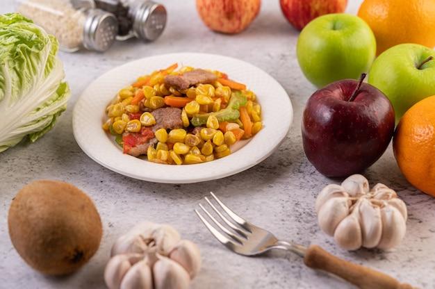 Wymieszaj kukurydzę i marchewkę, połóż wieprzowinę na talerzu na drewnianym talerzu.