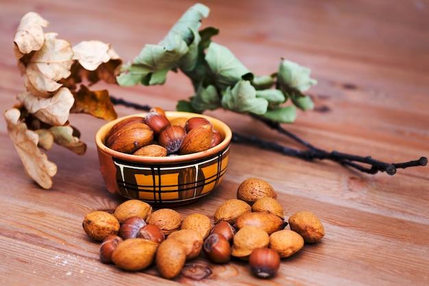 Wymieszaj orzechy z migdałami, orzechami laskowymi, orzechami włoskimi na drewnianym stole. miska z orzechami na drewnianym stole
