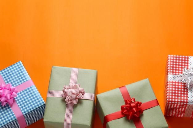 Wymieszaj pudełko na prezenty świąteczne umieszczone na pomarańczowej podłodze z papieru artystycznego i zostaw miejsce na kopię.