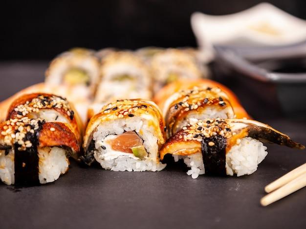 Wymieszaj różne rolki sushi na czarnym kamiennym backgorund w studio