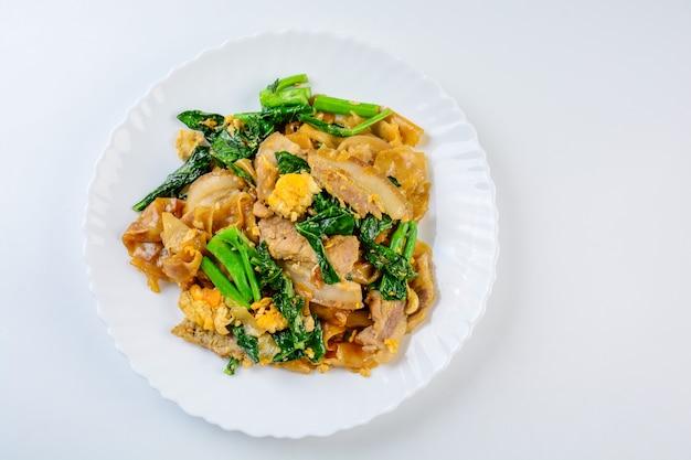 Wymieszaj smażoną mąkę ze świeżego ryżu, makaron z pokrojoną wieprzowiną, jajkiem i jarmużem, smaż smażony makaron,