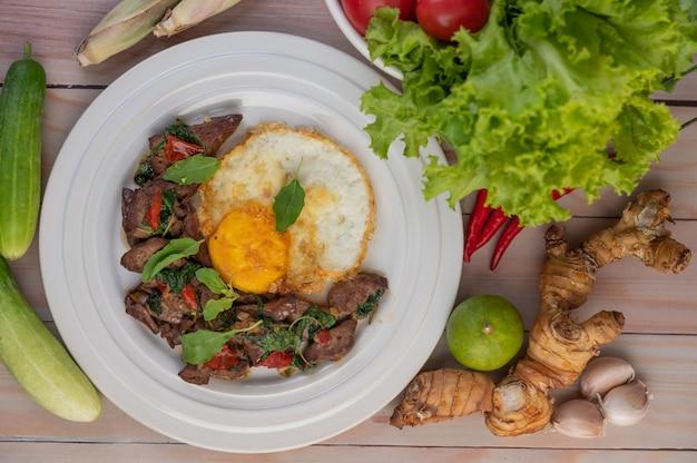 Wymieszaj smażoną wątróbkę bazyliową ze smażonym jajkiem na białym talerzu.
