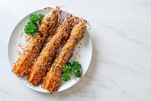 Wymieszaj smażone krewetki modliszki z czosnkiem na białym talerzu
