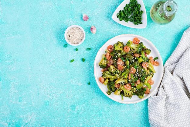 Wymieszaj smażone krewetki z brokułami z bliska na talerzu. krewetki i brokuły widok z góry, z góry