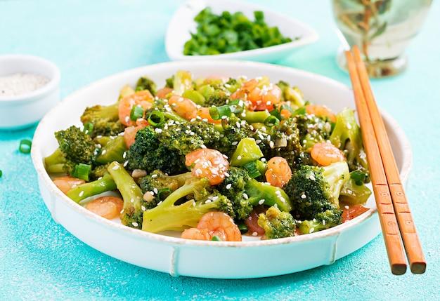 Wymieszaj smażone krewetki z brokułami z bliska na talerzu. krewetki i brokuły