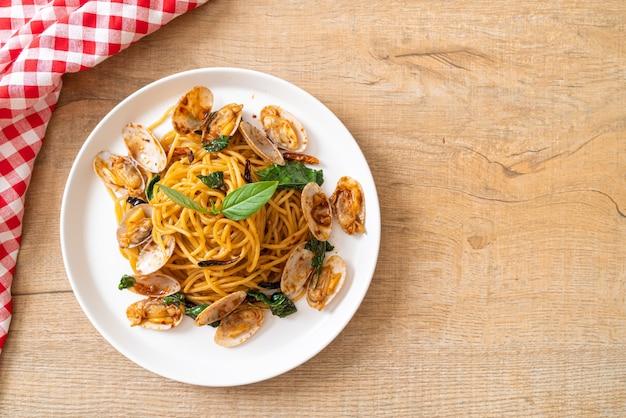 Wymieszaj smażone spaghetti z małżami, czosnkiem i chili