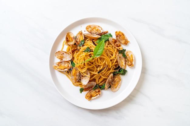 Wymieszaj smażone spaghetti z małżami i czosnkiem i chilli