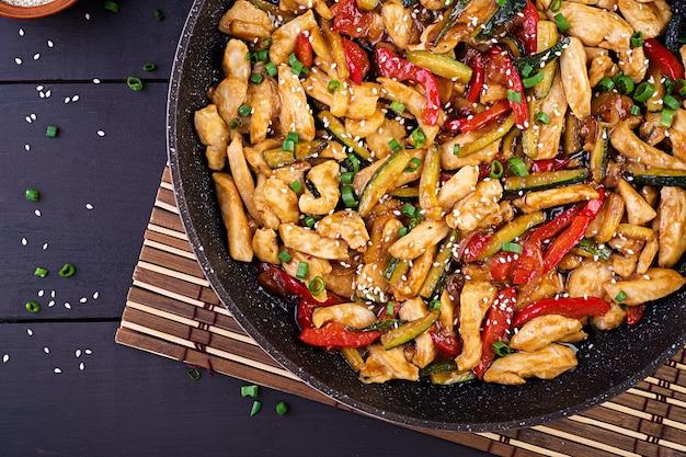 Wymieszaj smażonego kurczaka, cukinię, słodką paprykę i zieloną cebulę
