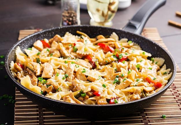 Wymieszaj smażonego kurczaka, makaron farfalle, cukinię, słodką paprykę i zieloną cebulę