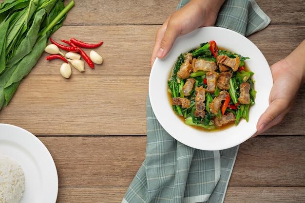 Wymieszaj smażony jarmuż, pikantną chrupiącą wieprzowinę na drewnianym stole. koncepcja tajskiego jedzenia.