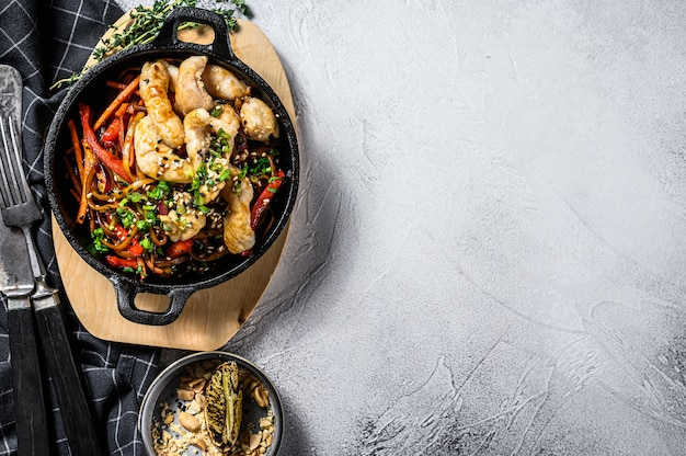 Wymieszaj smażony makaron z warzywami, kurczakiem. makaron wok. szare tło. widok z góry. skopiuj miejsce