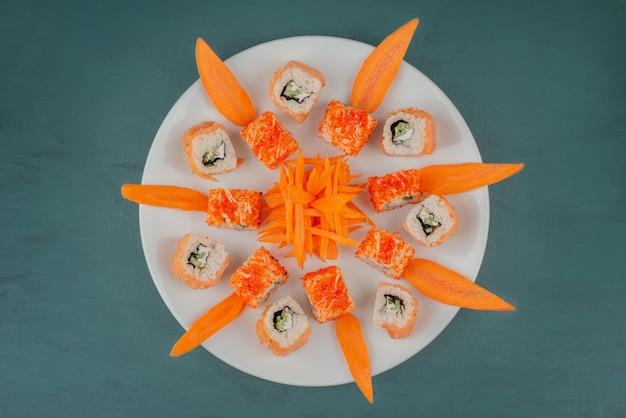 Wymieszaj sushi z plastrami marchwi na białym talerzu.