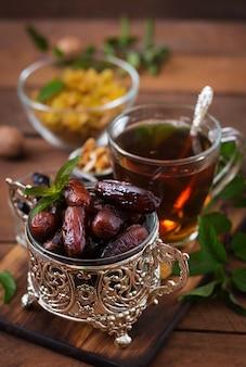 Wymieszaj suszone owoce (owoce palmy daktylowej, suszone śliwki, suszone morele, rodzynki) i orzechy oraz tradycyjną arabską herbatę. jedzenie ramadan (ramazan).