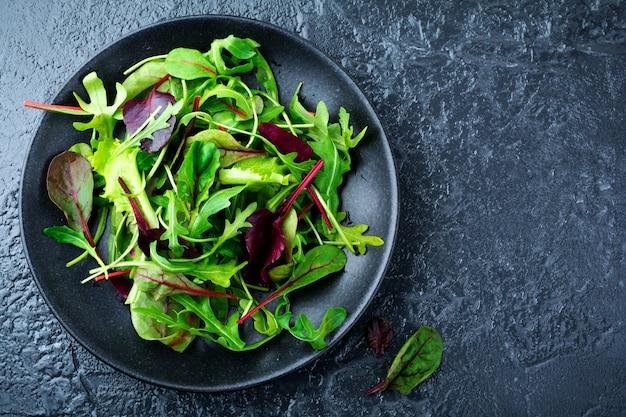 Wymieszaj świeże liście rukoli, sałaty, szpinaku, buraków do sałatki na ciemnej kamiennej powierzchni. selektywne skupienie.