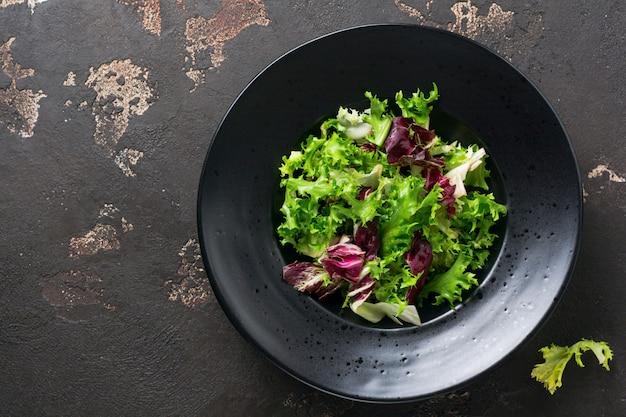 Wymieszaj świeże liście rukoli, sałaty, szpinaku, buraków do sałatki na ciemnym kamiennym tle