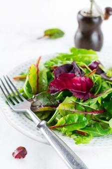 Wymieszaj świeże liście rukoli, sałaty, szpinaku, buraków do sałatki na jasnym, kamiennym tle. selektywne skupienie. widok z góry.