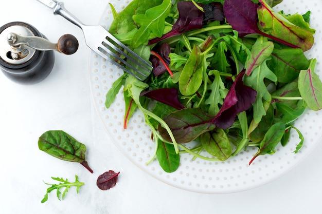 Wymieszaj świeże liście rukoli, sałaty, szpinaku, buraków do sałatki na jasnym kamiennym tle